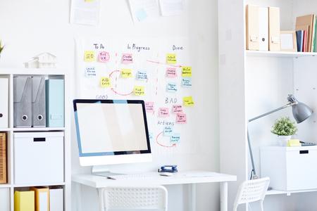 lugar de trabajo moderno con ordenador y notas adhesivas adhesivas de colores dispersos en la pared blanca Foto de archivo