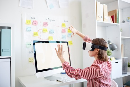 Unrecognizable woman exploring virtual reality in head-mounted display while sitting at computer in modern office