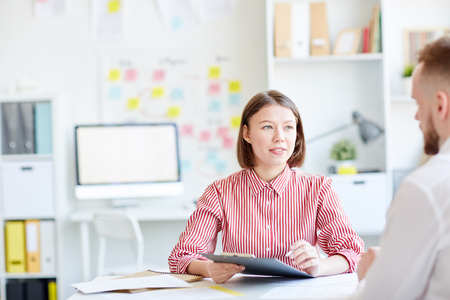Young attractive Caucasian female manager sitting at office desk and interviewing new male employee Stock Photo