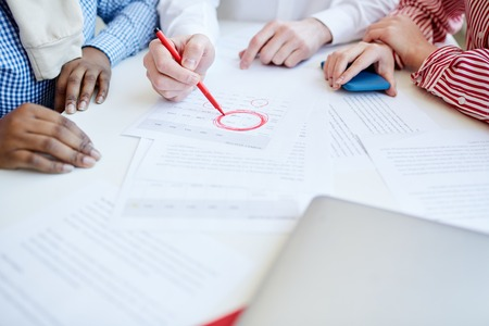 Group of unrecognizable people working with documents in office, highlighting important data with red marker