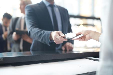 Hand van passagier die zijn documenten geeft dor inchecken aan manager door balie Stockfoto