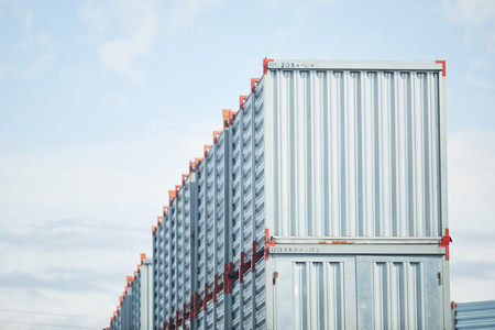 Top row of new metallic storage containers somewhere by load and transportation factory Imagens