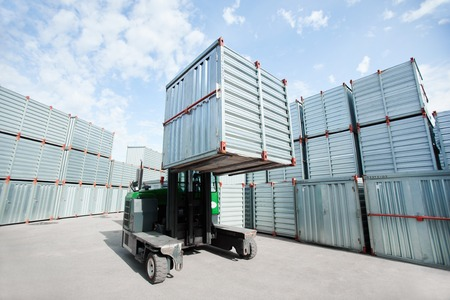 Special machine lifting large and heavy storage container and loading it Banco de Imagens - 102304880