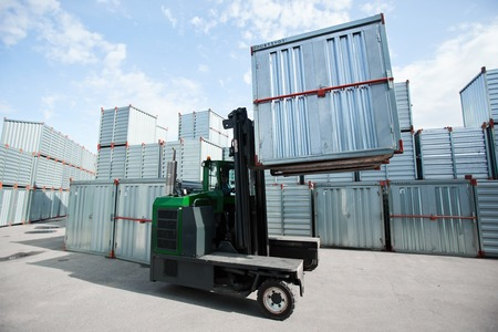 Load machine with one of storage container moving along territory of transportation company Reklamní fotografie