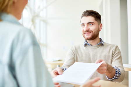Young man giving paper to person opposite