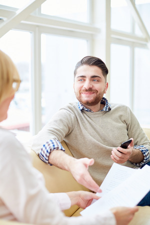 Smiling man having consultation with woman
