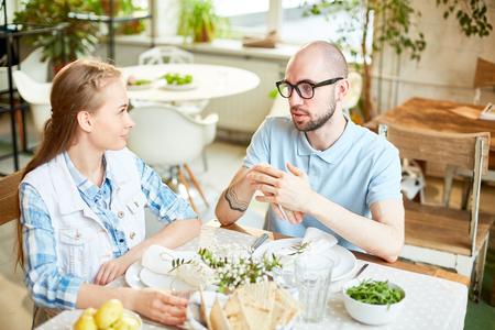 Man and young woman talking in cafe