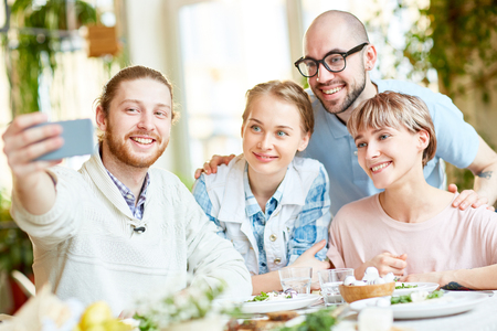 Smiling people taking selfie in restaurant Stock Photo