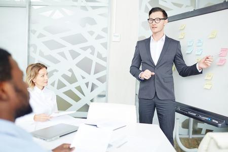 Employee showing presentation on blackboard