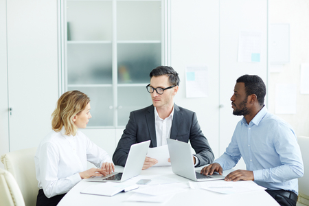 Office workers sitting at desk on meeting