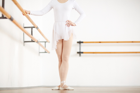 Faceless ballerina staying in position in white studio