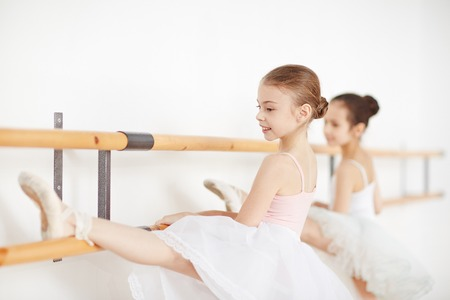 Young girls doing exercises on stretching in school Stock Photo