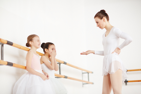 Teacher with strict hairstyle talking to young ballerinas