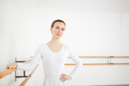 Graceful woman in white clothes looking at camera