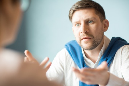 Displeased man talking to colleague