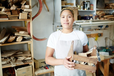 Adult woman in apron holding wooden box with tools and looking at camera while standing in carpenter workshop.