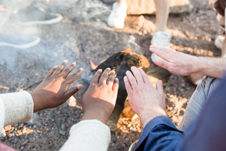 People warming hands over fire Stockfoto