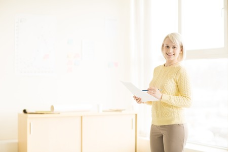 Female standing with document in office Stock Photo