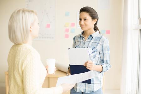 Females standing in office room talking
