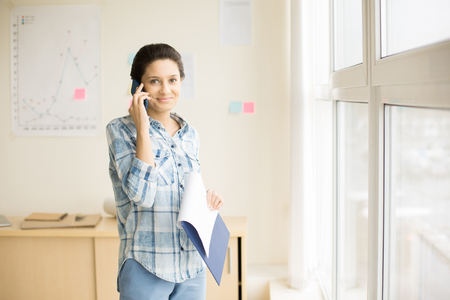 Woman talking on phone in office 版權商用圖片