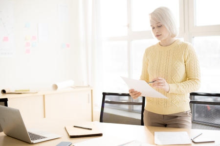 Woman reading document in office