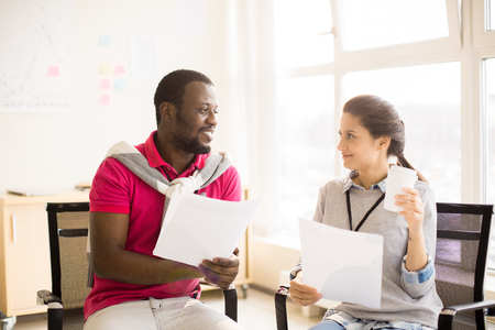Black man and young woman conversing on coffee break Stock Photo