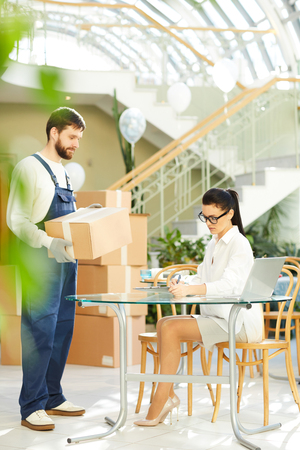 Female manager interacting with mover Stock Photo
