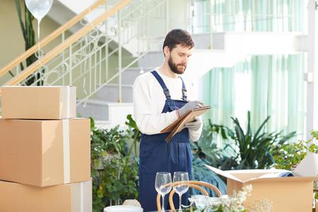 Contremaître d'entreprise de déménagement rédigeant des informations sur la livraison