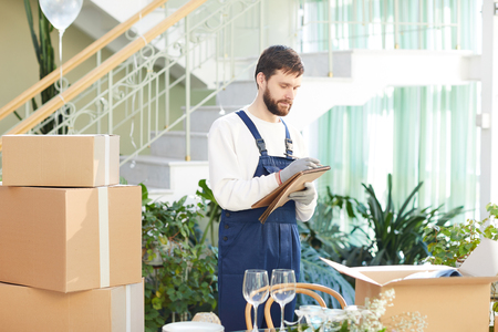 Moving company foreman writing information about delivery Stockfoto