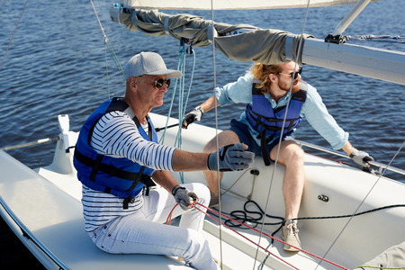 Father and son in sailboat Stock Photo