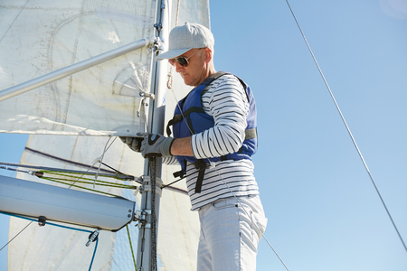Skilled sailor fixing mainsail on mast