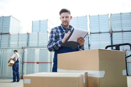 Cargo distribution worker checking boxes