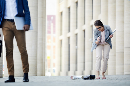Sad woman dropping stuff near office Stock Photo