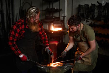 Blacksmiths forging iron Stock Photo