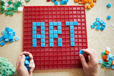 Above view of unrecognizable craftsman laying out  word ART in blue square tiles over red base on table, copy space Stock Photo
