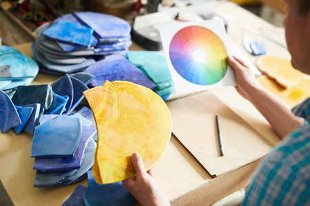 Portrait of unrecognizable artisan choosing color palette holding swatches while sitting at table in modern workshop, copy space 写真素材