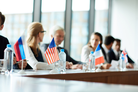 Small national flags on conference table Stock Photo