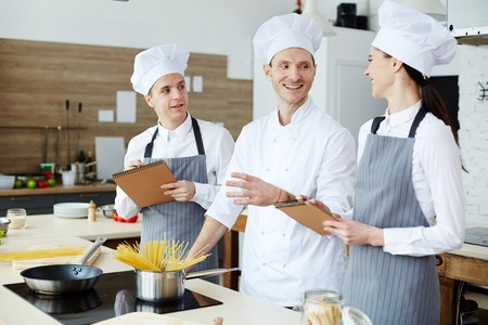 Cheerful cooking specialists discussing pasta recipe Banque d'images - 105504107