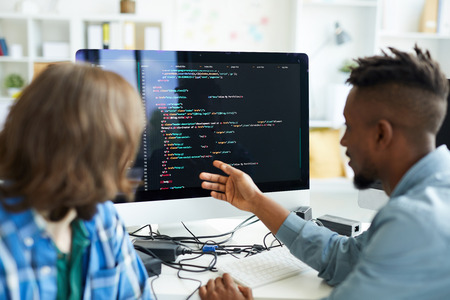 Busy colleagues analyzing computer code