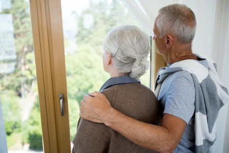 Loving Senior Couple Looking at Window Banque d'images