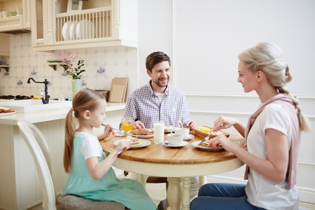 Smiling family members eating pancakes