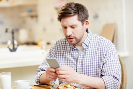 Concentrated man using smartphone at breakfast 版權商用圖片