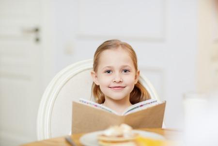 Smiling girl reading book in kitchen 版權商用圖片