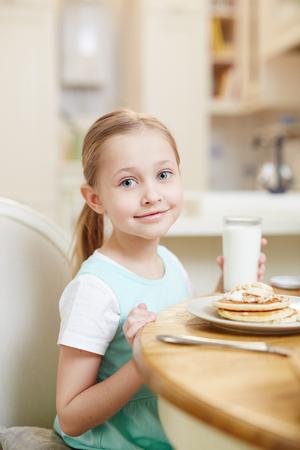 Cute girl drinking milk with pancakes 版權商用圖片