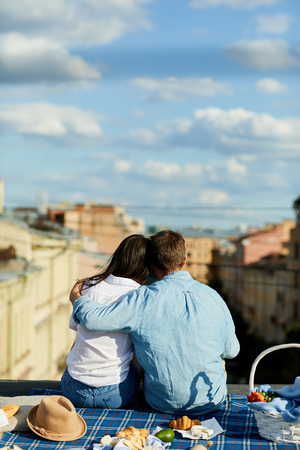 Rear view of young couple in casual shirts sitting on blanket and embracing while looking into distance and dreaming together at picnic on roof