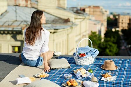 Dreamy girl having lunch on roof Foto de archivo - 105859749