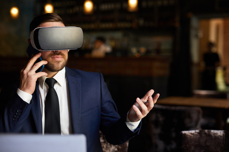 Modern businessman in VR headset talking on phone Stock Photo