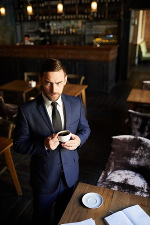 Frowning businessman standing at table and drinking coffee Stockfoto