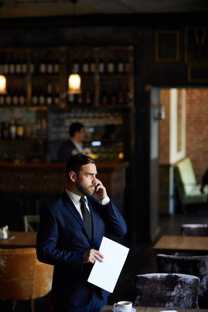 Restaurant manager talking on mobile phone