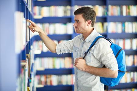 Student guy finding book on shelves Zdjęcie Seryjne